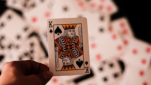 King of Spades card held over a deck of cards