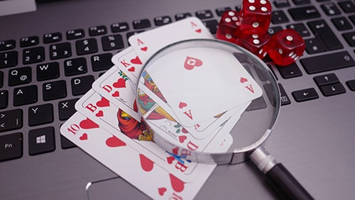 Laptop with playing cards, dice and magnifying glass. Concept of online gambling