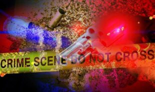 Gun on the sand with a crime scene tape concept