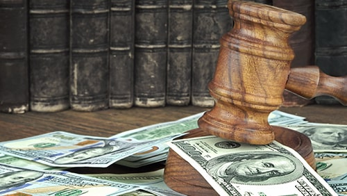 Judges Gavel And Scattered Money Heap On Wooden Table Close Up