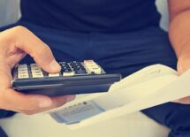 closeup of a man checking payroll with a calculator