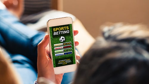Man laying on a couch holding his mobile phone with sports betting app open