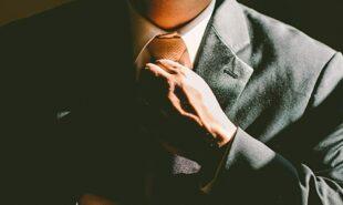 Business man adjusting his necktie