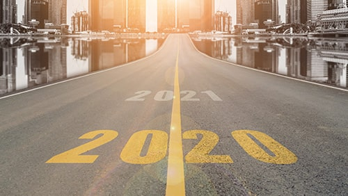 The number 2020 symbol represents the new year on the road heading to the city with beautiful skyscrapers background,