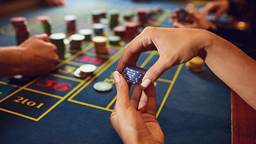Gamer play casino roulette at a table in a casino.