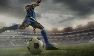 Save Download Preview Professional football or soccer player in action on stadium with flashlights, kicking ball for winning goal