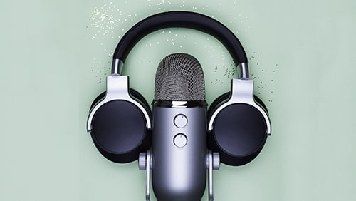 Microphone and headphones on mint table with gold glitter