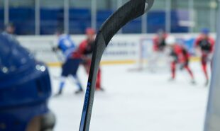 Close up of a hockey stick against a hockey game background