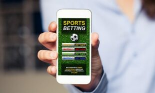 Hand holding a mobile phone with a sports betting app open