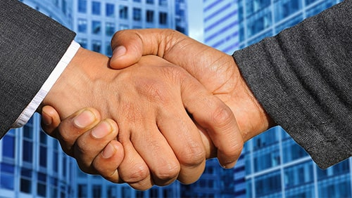 Zoomed photo of hands shaking against a background of business buildings