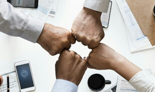 Four different hands bumping fists. Concept of partnerships