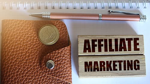 Affiliate marketing typed on wooden blocks, wallet, coins, pen. Business concept