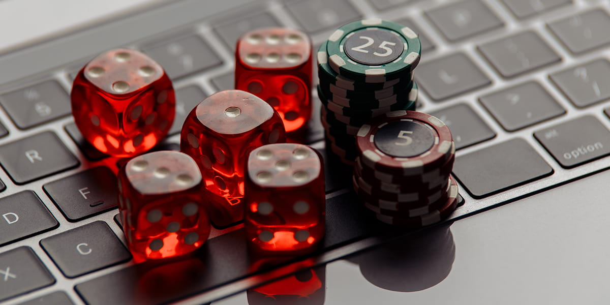 Online casino concept. Gambling chips and five red dices on laptop keyboard close-up