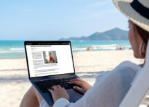 Mockup image of a woman using and typing on laptop computer in the beach
