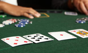 Playing cards chips and players gambling around a green felt poker table