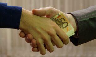 Two men shaking hands with money in between their hands