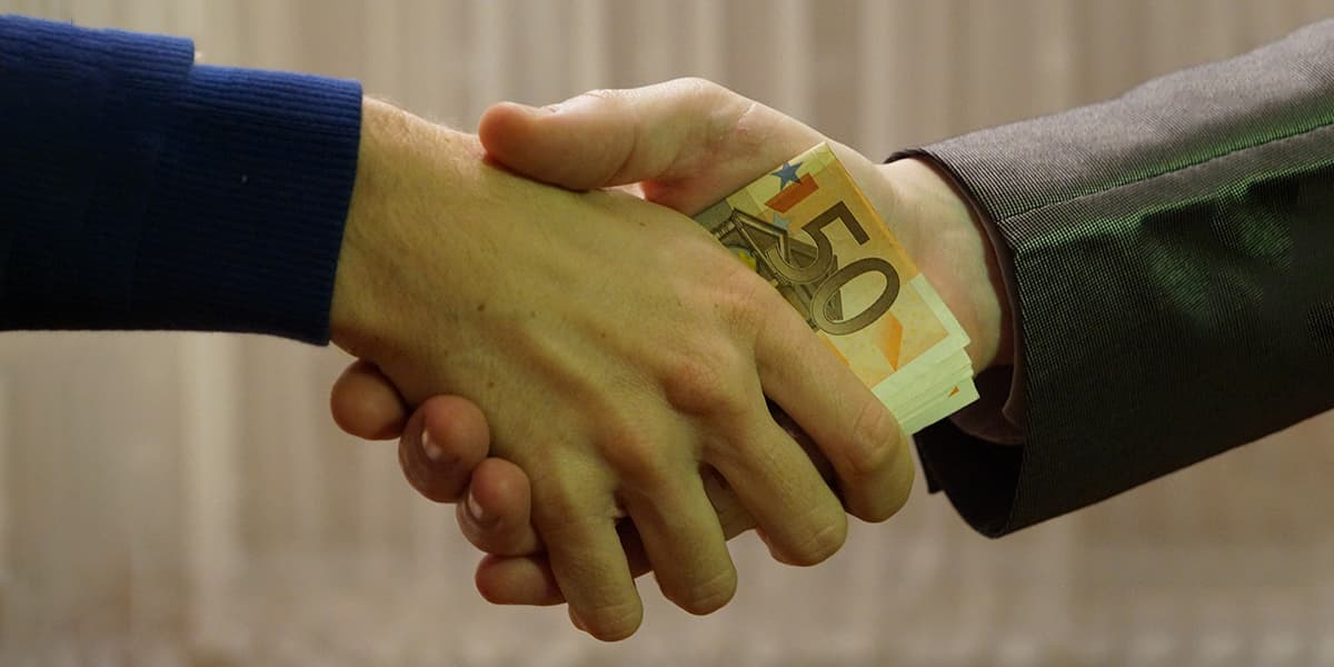 Two men shaking hands with money in between their hands