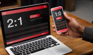 Close up laptop and smartphone screen with mobile app for betting and score.