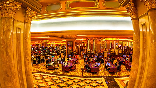 Aerial view of black jack tables and gamblers inside of a Casino in Macau
