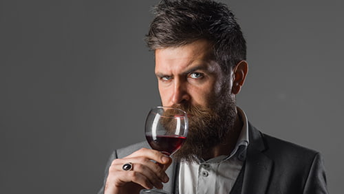 Bearded man with alcohol. Man in suit drinks wine. Alcohol