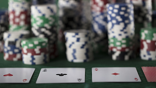 Casino theme, cards and stack of chips on glass table