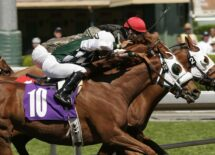 Close-up of three jockeys racing neck and neck toward the finish line in a thoroughbred horse race