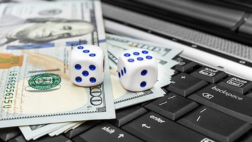 Dice with money on the laptop keyboard