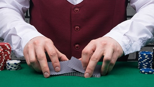 the dealer's hands are holding a deck of cards and placing chips on the poker table