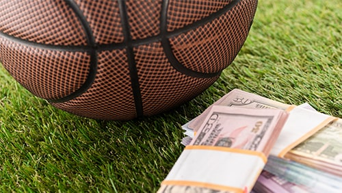 Close-up view of basketball ball near dollar and euro banknotes on green grass, sports betting concept