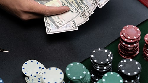 Close up of a poker table with chips and a hand holding cash
