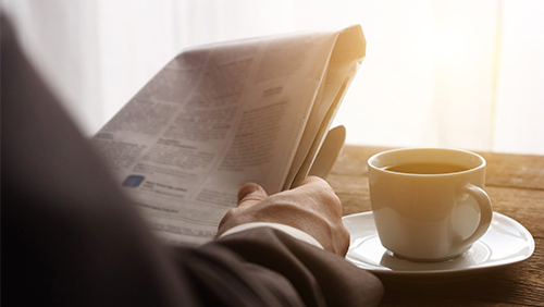 Businessman reading newspaper with coffee in the morning