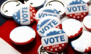"""""""Vote"""" pins on top of the USA flag"""