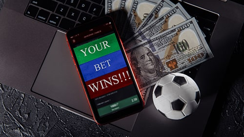 Smartphone with gambling mobile application, ball and money banknotes on a keyboard.