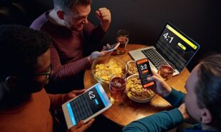 Excited fans in bar with beer and mobile app for betting, score on their devices.
