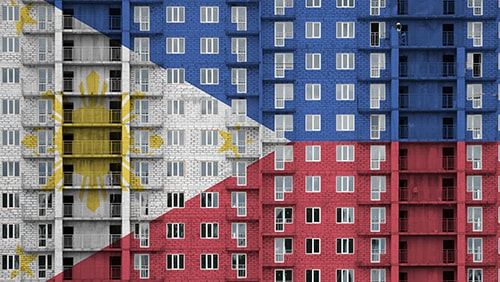 Philippines flag depicted in paint colors on multi-storey residental building under construction.