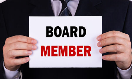 businessman holding board member sign