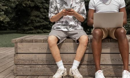 Two men using mobile devices and laptop sitting on a bench