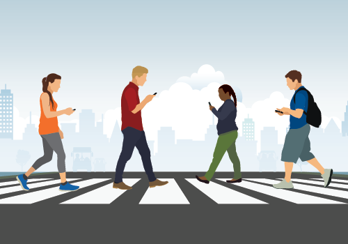 A group of people crossing the road using mobile phones