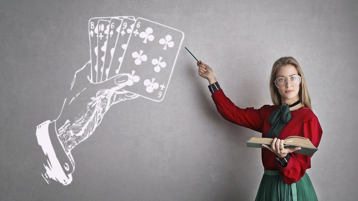 A teacher pointing a drawing of playing cards and a hand on a blackboard