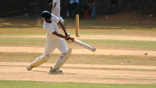 Seorang pemain kriket sedang memukul bola
