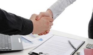 Handshake of business partners, when signing documents. Isolated on white background