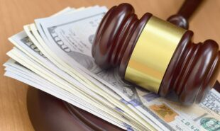 Judge gavel and money on brown wooden table.