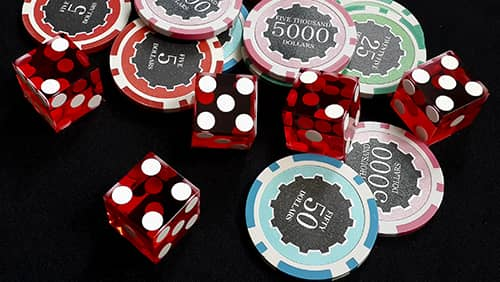 Five red dice and stacked of chips bet many value on black fabric Gambling devices and casino concept
