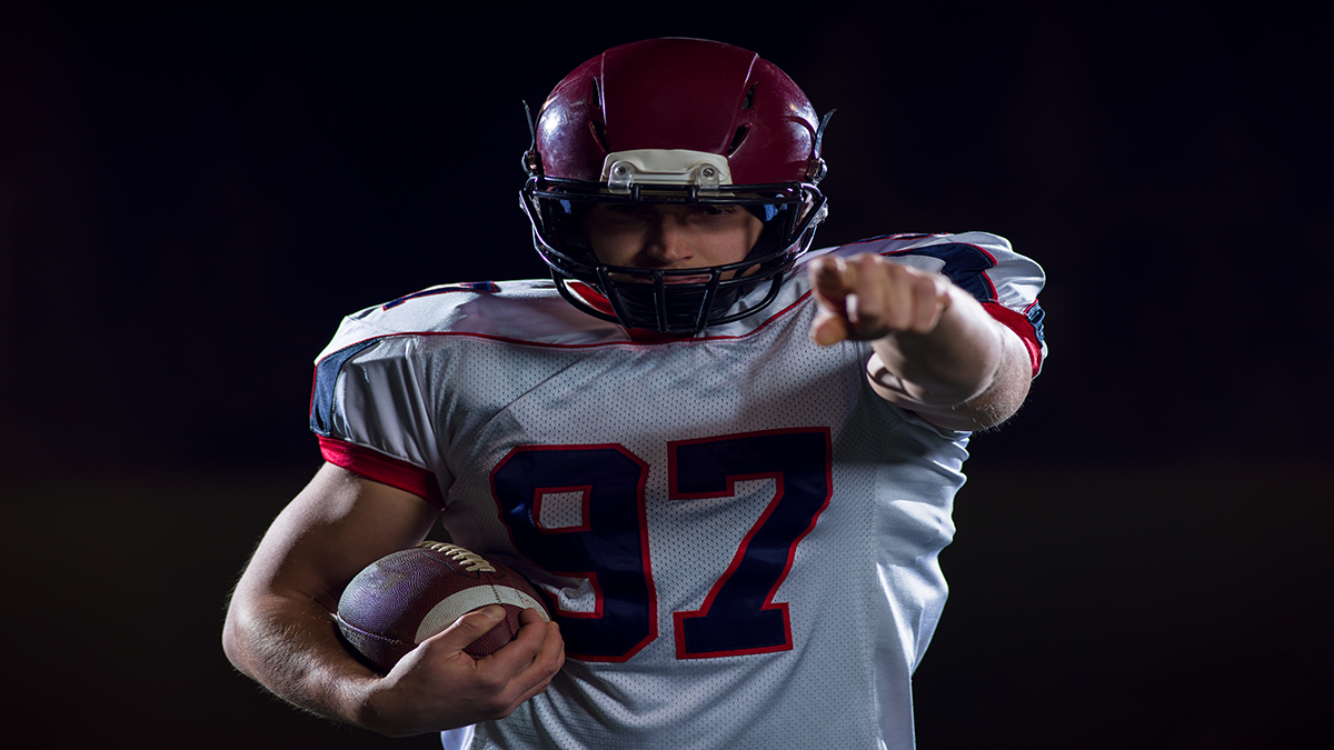 portrait-of-confident-american-football-player-holding-ball-while-standing-on-field-at-night