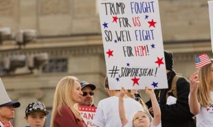 Protesters at \'Stop the Steal\' rally holding signs for honest election and in support of Donald Trump
