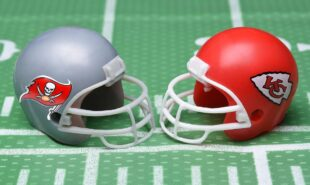 Helmets for the Tampa Bay Buccaneers, and Kansas City Chiefs, opponents in Super Bowl LV. on a green football field background