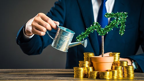 A business man watering a plant with gold coins on its side. Investment concept.