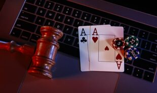 Wooden judge gavel and aces on keyboard of laptop
