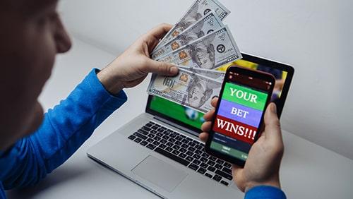 Pemenang pria yang beruntung di taruhan sepak bola dengan uang dolar dan telepon di tangan.