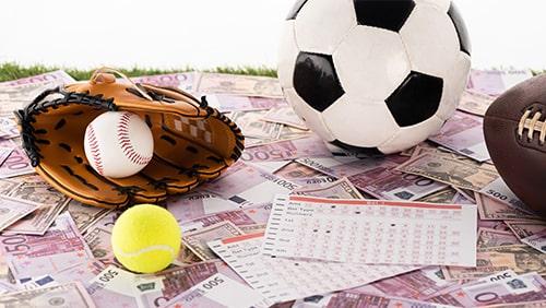 sarung tangan bisbol dan bola, sepak bola, tenis dan bola rugby di dekat daftar taruhan pada uang kertas euro dan dolar